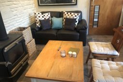 Cosy sofa area in pottery studio with wood burner